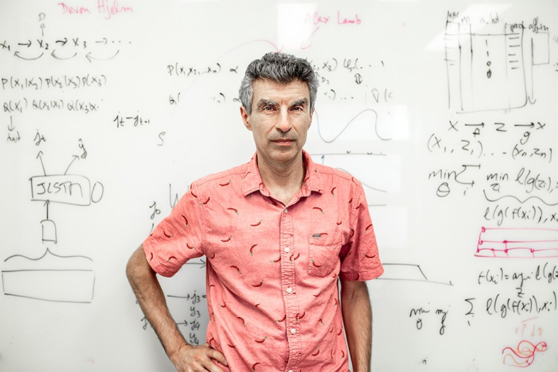 Yoshua Bengio in front of a board filled with equations