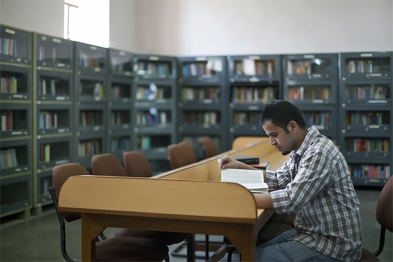 Young man reading in a library in India