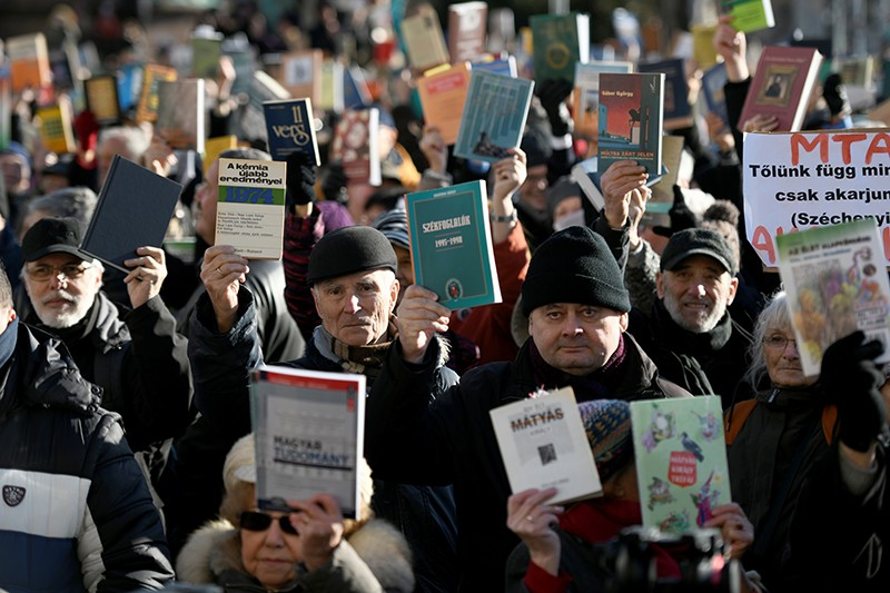 People raise science books in protest outside of the Hungarian Academy of Sciences in Budapest.