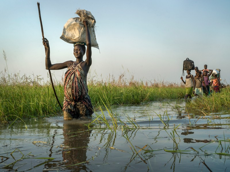 A pregnant woman walks through a swamp in South Sudan, carrying a bag on her head