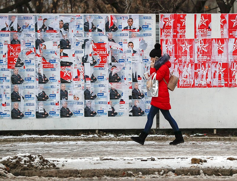 A woman walks past a panel with election campaign posters in downtown Chisinau, Moldova.