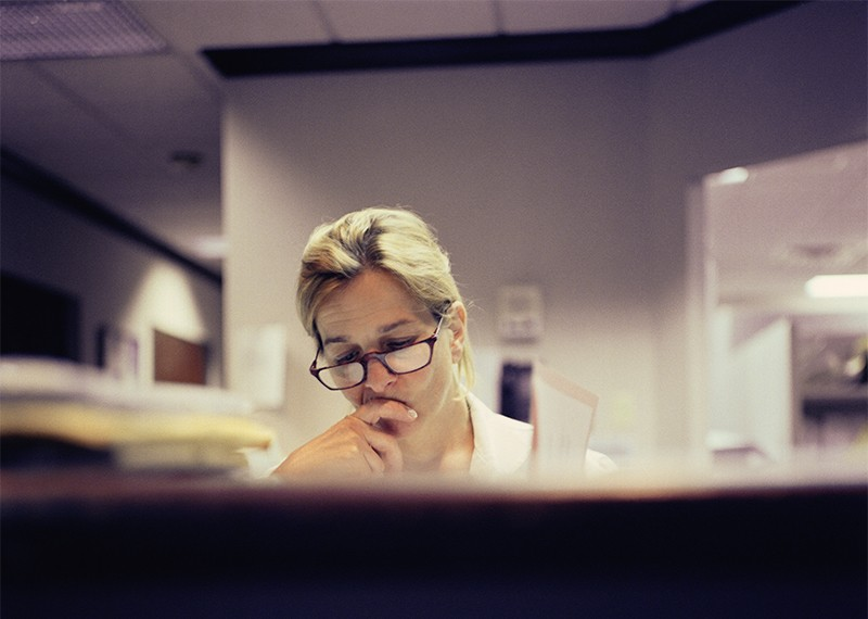 A medical professional looking tired in an office