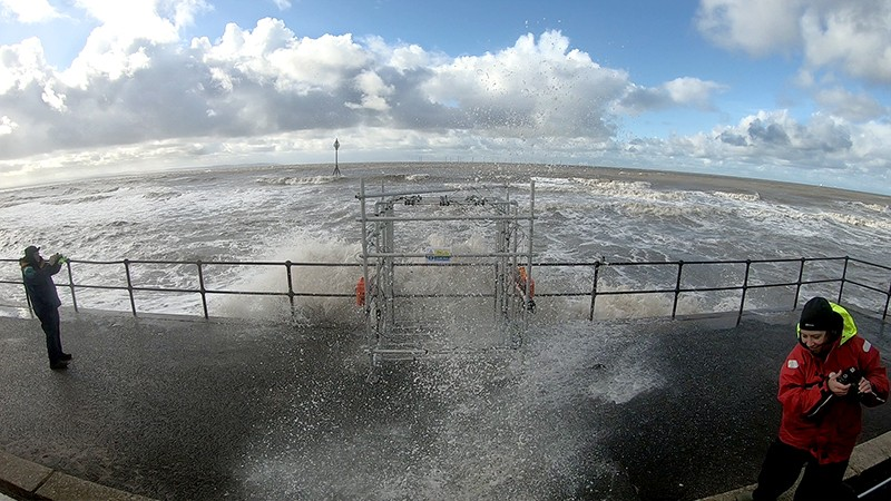 WireWall structure is hit by a wave at the seawall while NOC scientists record data to the left and right