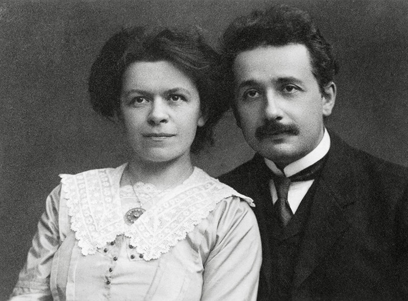 Black and white photo of young Einstein (right) and his wife in Edwardian clothes.