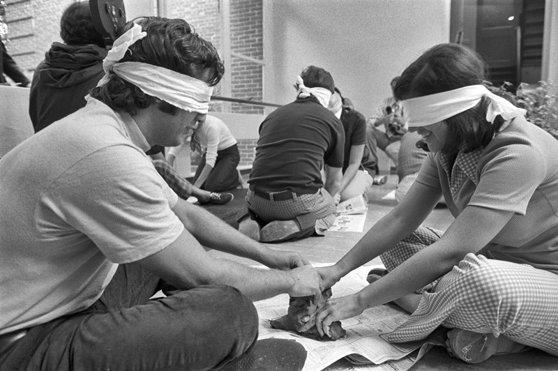 Black and white photo of participants in behavioural science experiment blindfolded and playing with clay