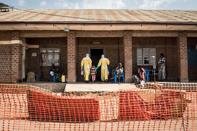 Medical workers lead a young girl into the unconfirmed Ebola patients ward in Beni, northeastern DRC.