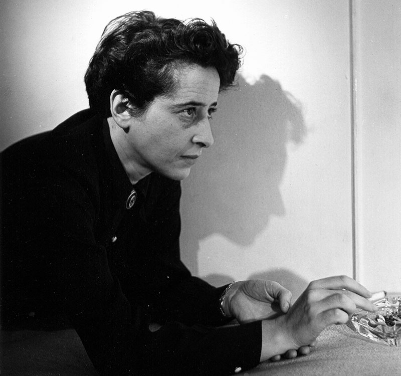 A black and white photo of Hannah Arendt in profile, leaning over a table and smoking a cigarette.
