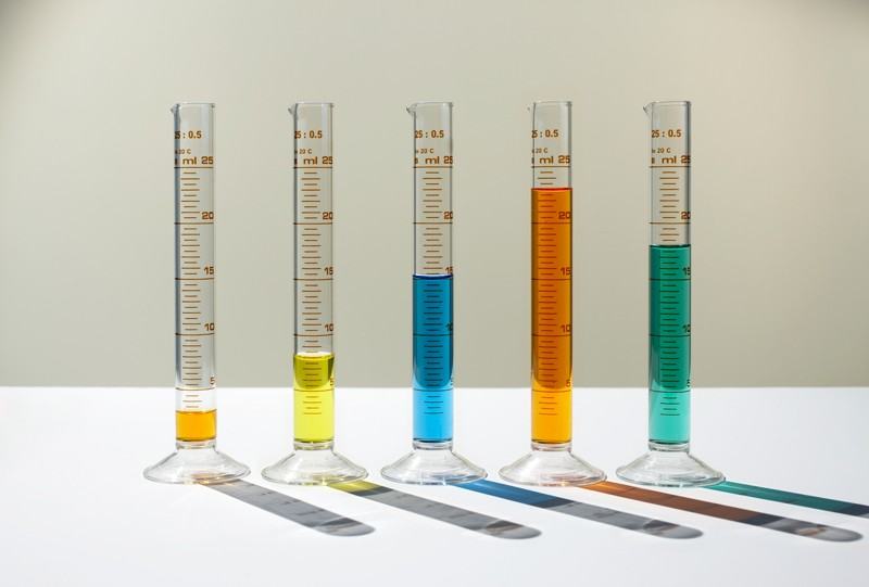 Bar chart made of measuring cylinders filled with different amounts of varied coloured liquids