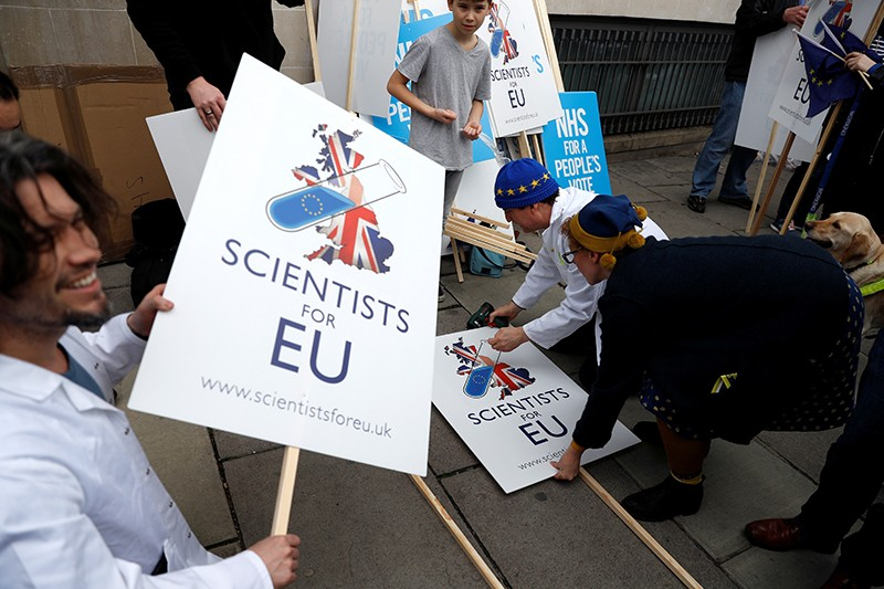 EU supporters hold signs saying 'Scientist for EU' as they prepare to participate in the 'People's Vote' march in central London