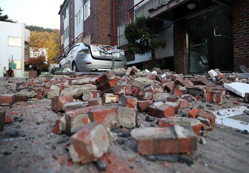 Bricks and debris from damaged buildings lie on the ground in front of a damaged car in Pohang, South Korea
