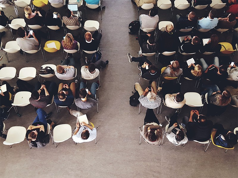 Overhead photograph of people sitting In an auditorium