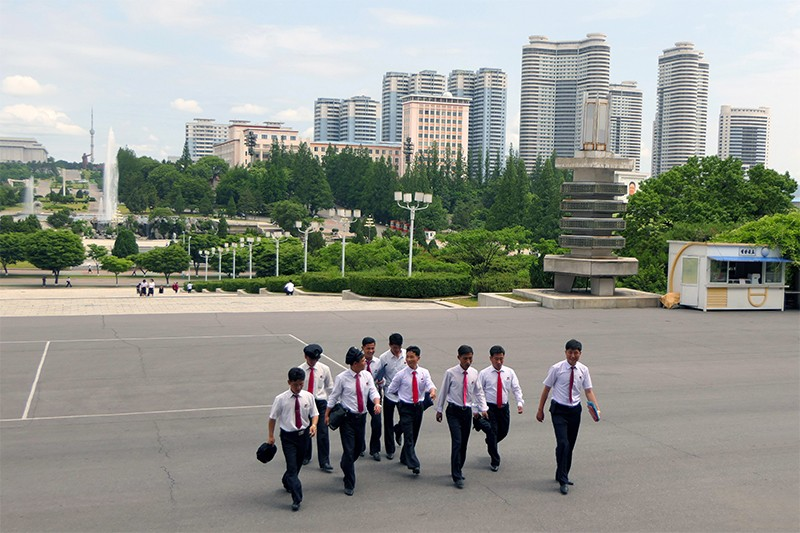 Students walk across Kim Il-sung Square with Pyongyang city in the background.