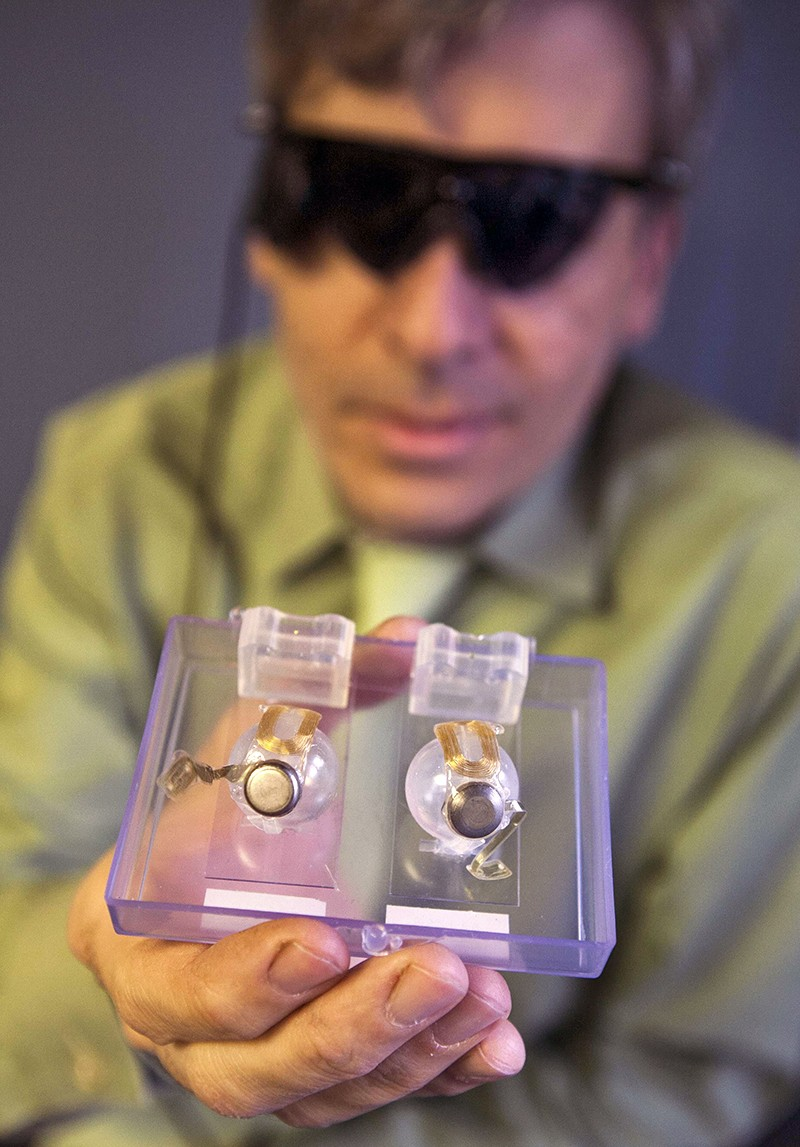 A patient wearing dark glasses holds up the Argus II implant