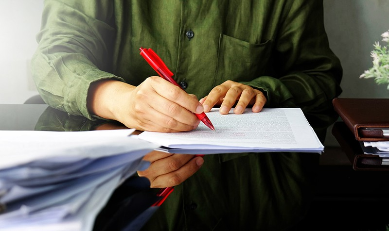A Hand holding a red pen writing on white paper.
