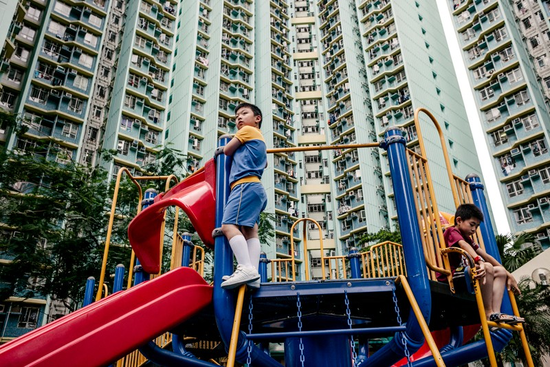 Children play in a small park at the base of a highrise residential block in Hong Kong