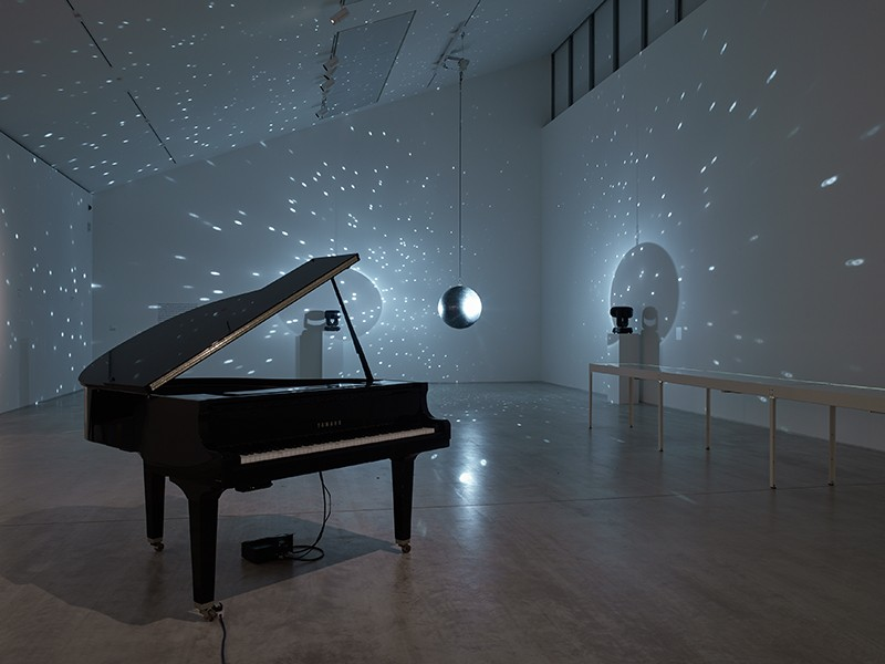 A grand piano stands in a darkened room. Behind it, a mirror ball casts dots of light onto the white walls.