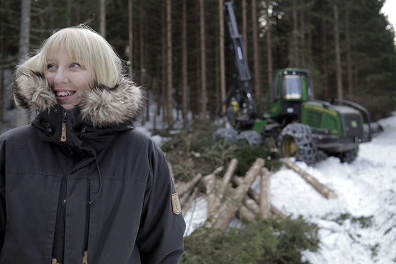 A woman in a winter coat stands in snow in front of a forest, where trees are being cut down.