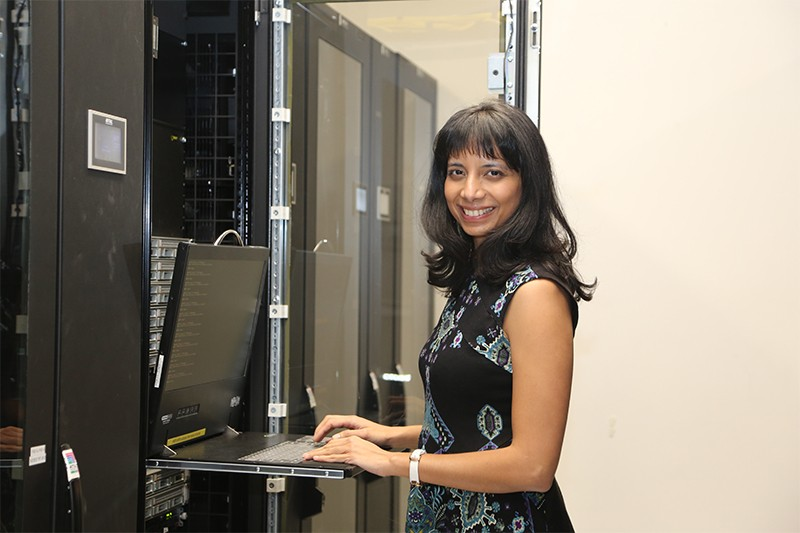 Anima Anandkumar smiles while typing on a laptop in front of servers at Caltech