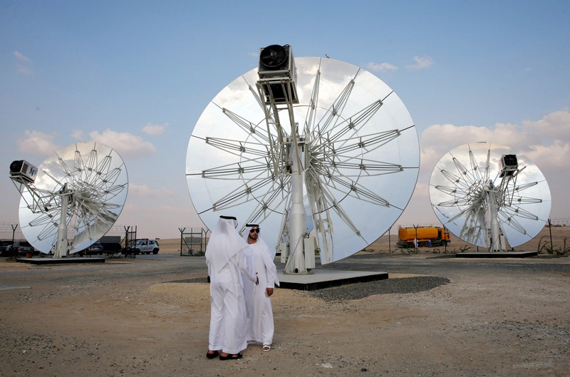 Men stand in front of circular solar panels at a solar park in Dubai