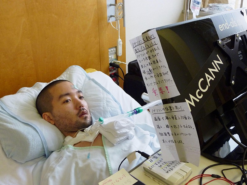 Masahiro Fujita in a hospital bed, with a breathing tube. In front of him is a monitor plastered with Japanese signs.