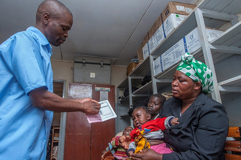 A health surveillance assistant shows a health passport for a mother and her child at a malaria-vaccine screening.