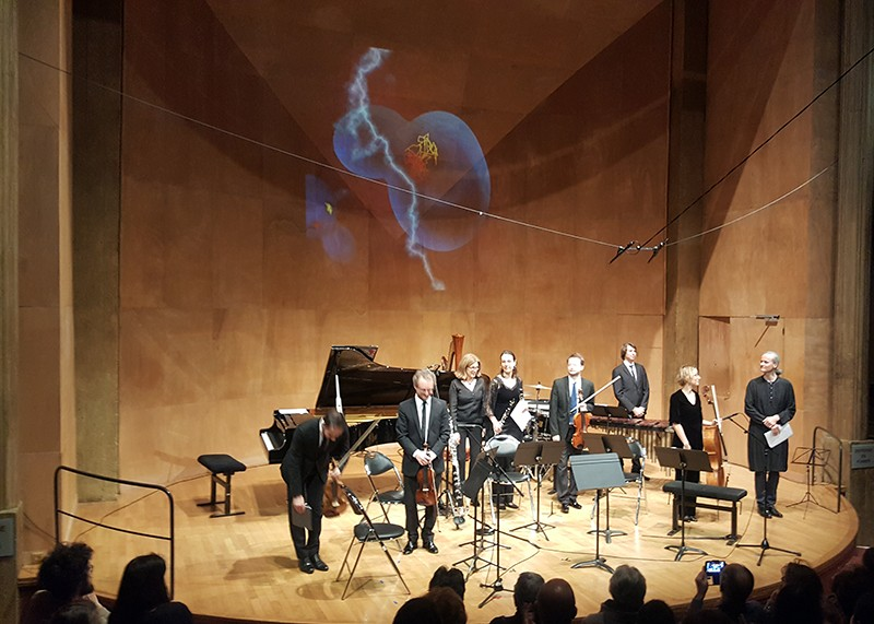 Seven musicians on a stage, with a scientific image projected onto the wall behind them.