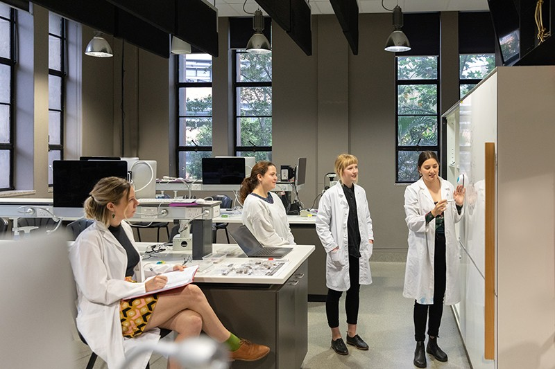 four female scientists in a laboratory with one teaching the research from a whiteboard