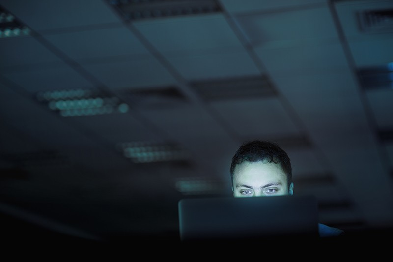 Man looking at laptop computer in office at night