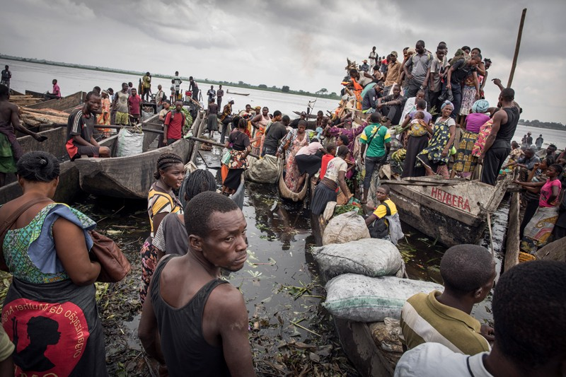 A busy riverside with moored boats and stalls selling food at Mbandaka in the Democratic Republic of Congo