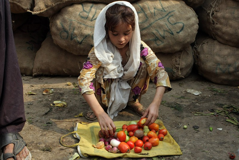 A Pakistani girl sells tomatoes in a market in Lahore, Pakistan
