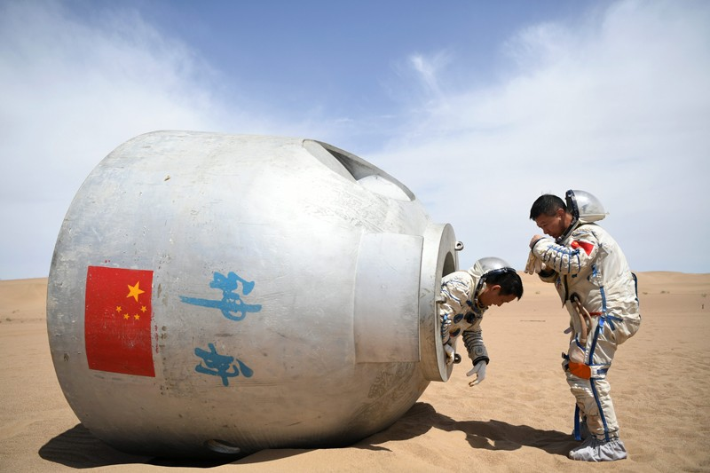 Chinese astronauts Nie Haisheng and Liu Wang exit from a re-entry capsule during a wilderness survival training in China
