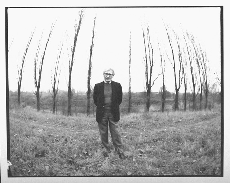 A black and white photo of James Lovelock standing in front of a row of bare trees.