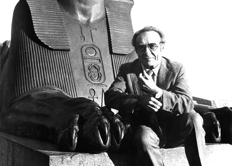 A black and white photograph of Jacob Bronowski sitting between the paws of a stone Egyptian sphinx.