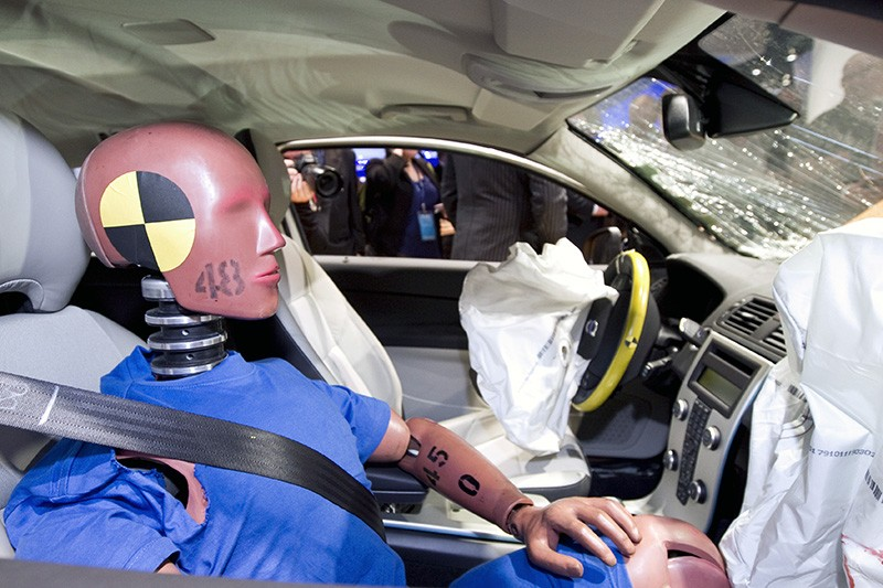 A crash test dummy on display in a vehicle that was test-crashed