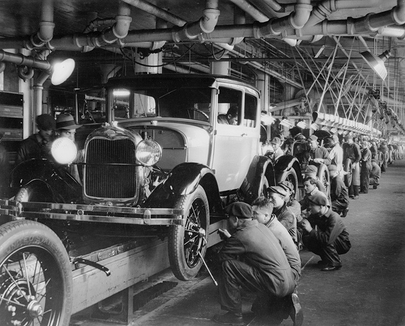 A black-and-white photo of cars in a production line.