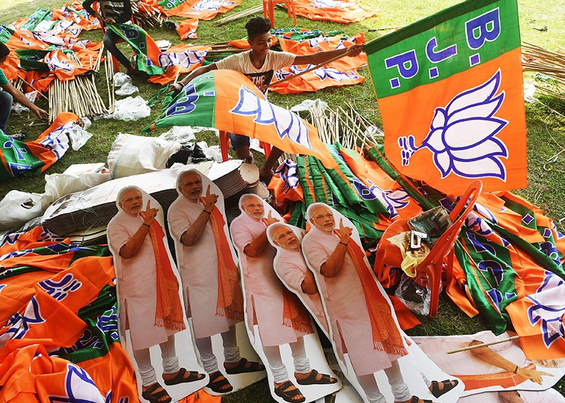 Indian labourers arrange Bharatiya Janata Party (BJP) flags and cut-outs of Indian Prime Minister Narendra Modi