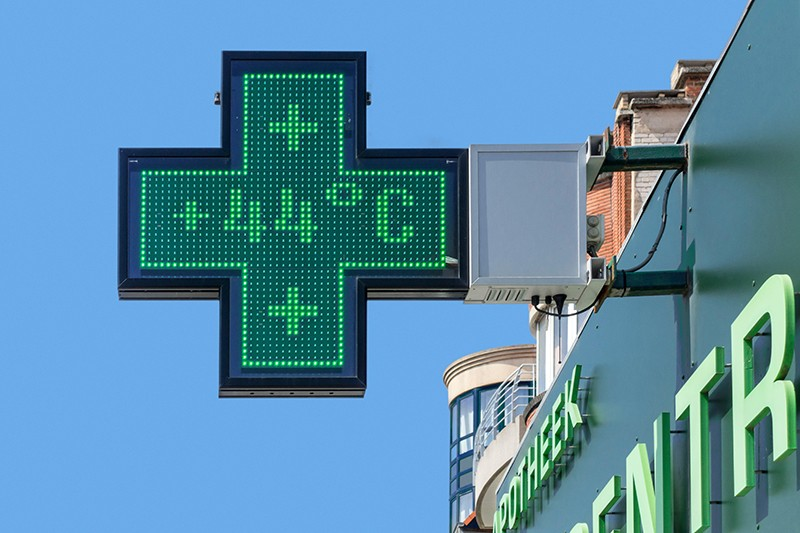 Thermometer in green pharmacy screen sign displays extremely hot temperature of 44 degrees Celsius during heatwav