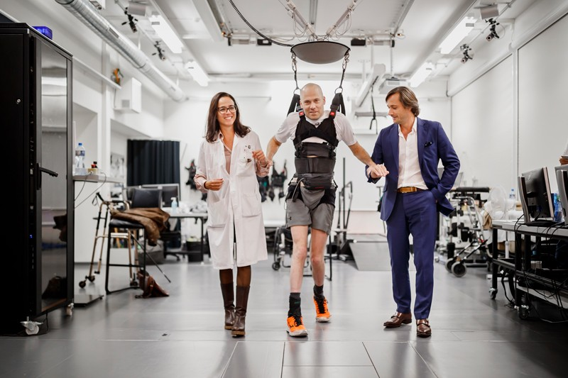 Swiss paraplegic patient Sebastian Tobler, walks in a harness with Professor Gregoire Courtine and Professor Jocelyne Bloch