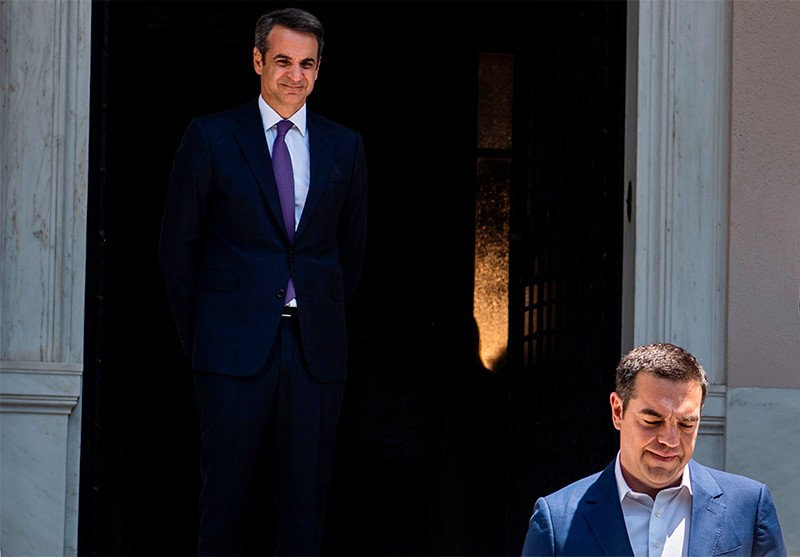 Greece's new Prime Minister Kyriakos Mitsotakis watches his predecessor Alexis Tsipras leave the Maximos Mansion