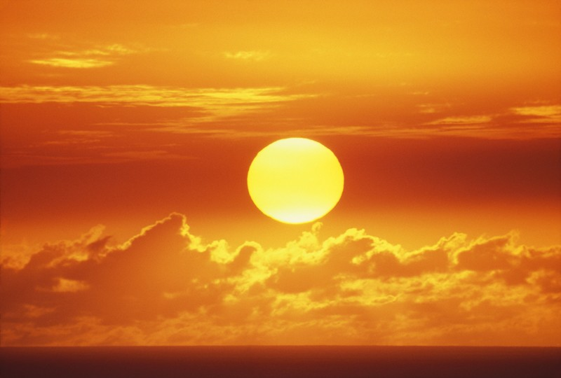 A huge orange sun sinking towards the horizon