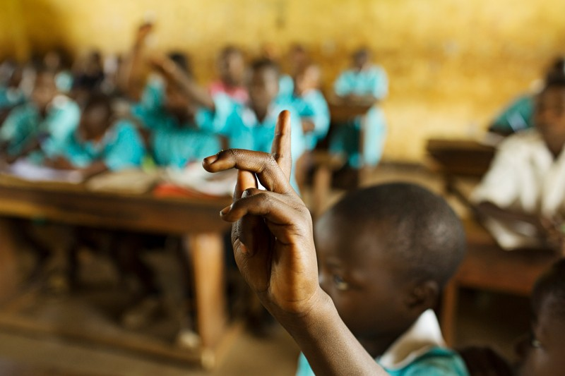 Pupils at a school in Uganda hold up their hands in class