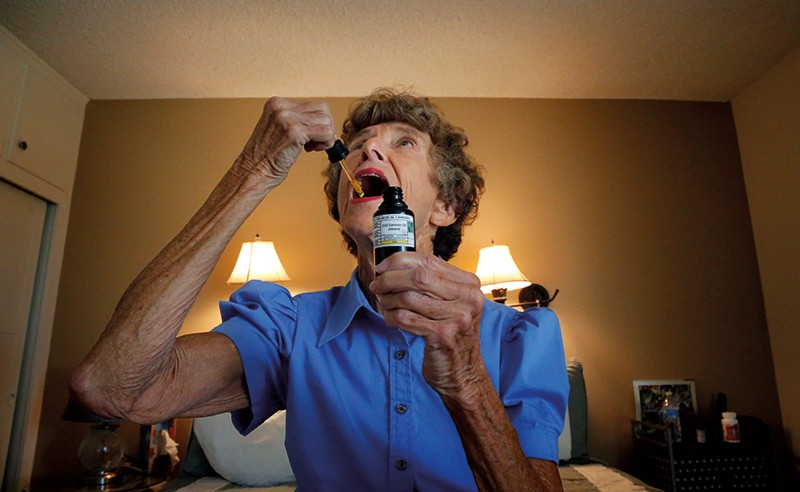 A woman doses herself with some cannabis oil