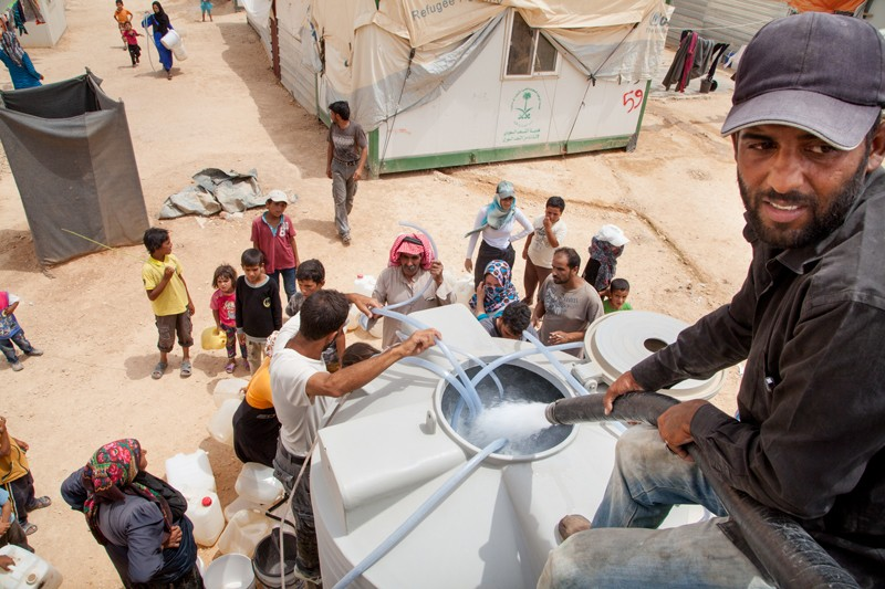 Water is distributed to refugees at the Zaatari Refugee camp near the Syrian border in Jordan