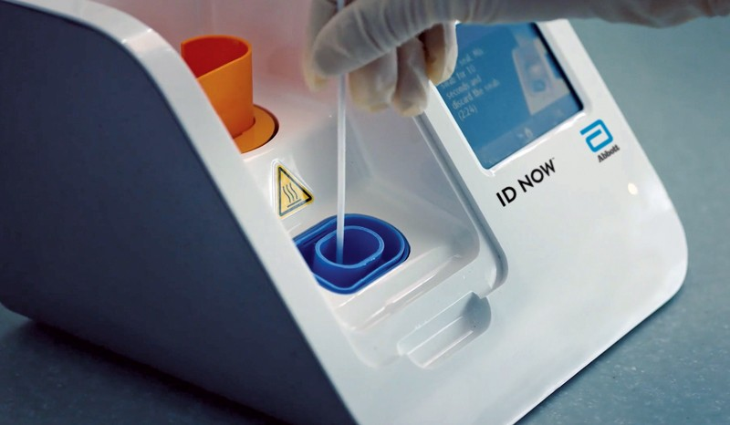 A hand inserts a sample into ID Now machinery