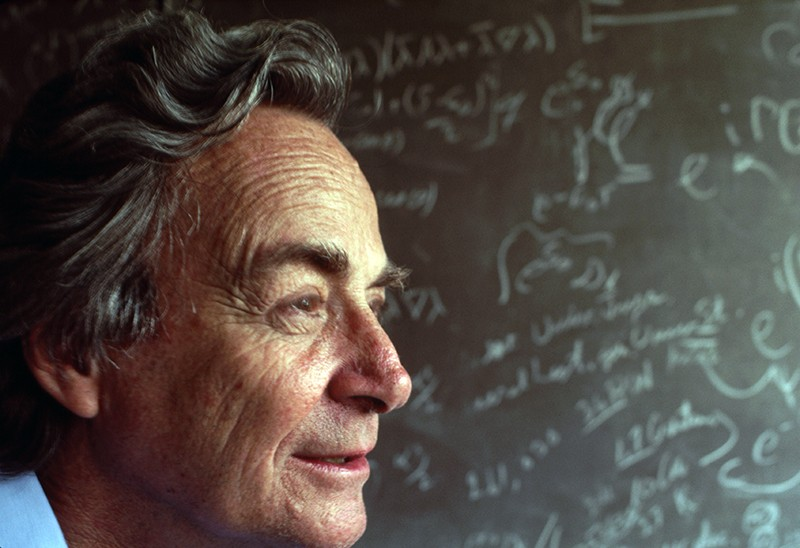 Richard Feynman stands in front of a blackboard strewn with notation in his lab in Los Angeles, in 1983
