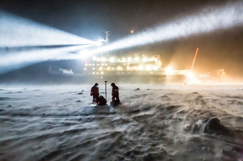 AWI sea ice physicists work on the sea ice in wind and snow during an expedition to the Antarctic
