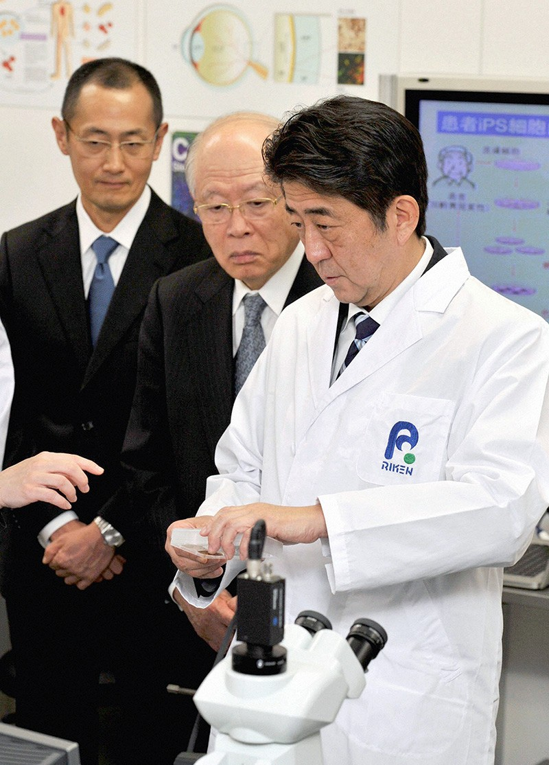 Japanese Prime Minister Shinzo Abe (right) and Shinya Yamanaka (left) at a Riken lab in Kobe, Japan