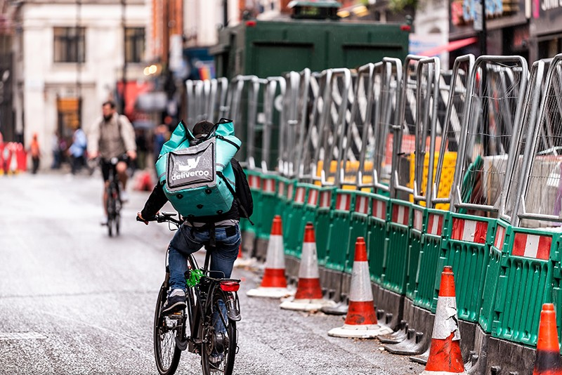 Deliveroo biker traversing the streets in London.