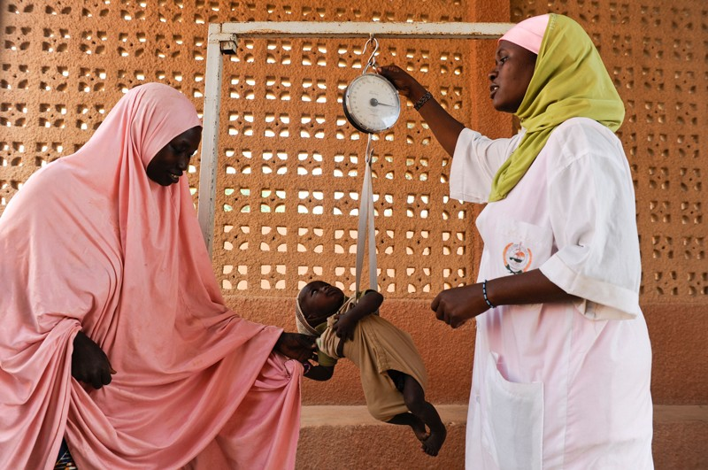 A baby is weighed as part of a nutrition project in Zinder, Niger.