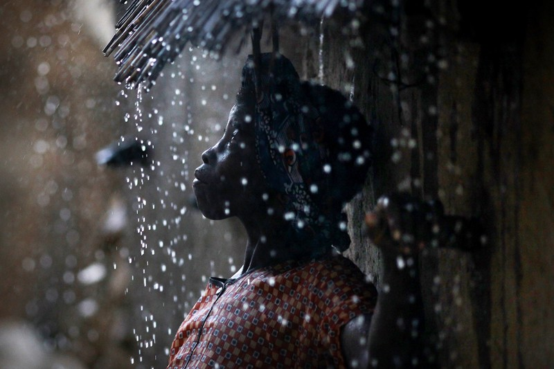 A Dogon woman shelters from the rain